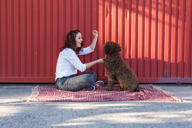 Mooie jonge vrouw die haar hond, een bruine spaanse waterhond koestert. ze lacht en houdt van de hond. liefde voor dieren