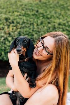 Mooie jonge vrouw die haar hond knuffelt