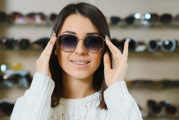 Mooie jonge vrouw die haar nieuwe zonnebril aanpast die zich in optische opslag bevindt
