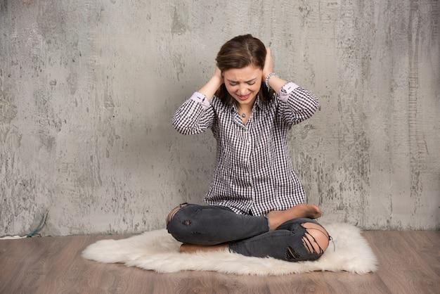 Mooie jonge vrouw die haar oren bedekt met haar handen en haar ogen sluit.