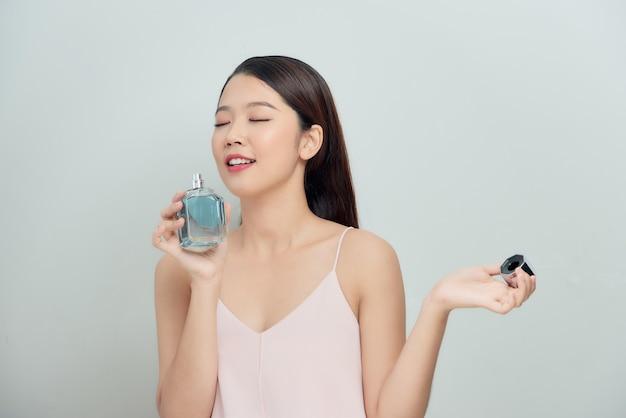Mooie jonge vrouw die haar parfum ruikt