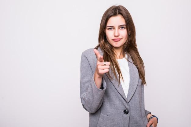 Mooie jonge vrouw die haar vinger richt die op witte achtergrond wordt geïsoleerd