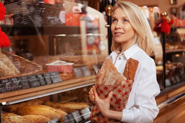Mooie jonge vrouw die heerlijk vers brood koopt bij de bakkerij, exemplaarruimte