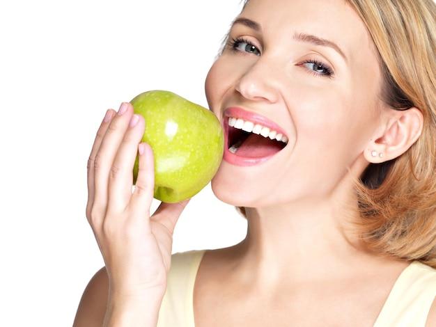 Mooie jonge vrouw die het bijten van een verse rijpe appel - op witte muur bijt.