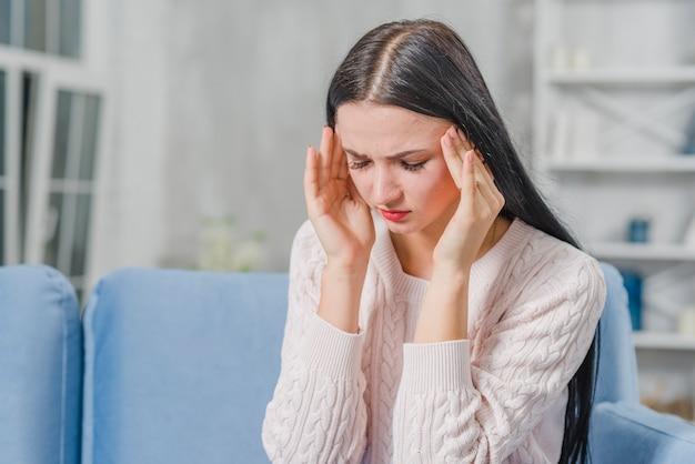 Mooie jonge vrouw die hoofdpijn heeft