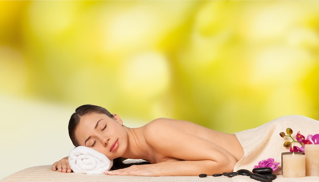 Mooie jonge vrouw die hotstone-massage ontvangt in salon spa