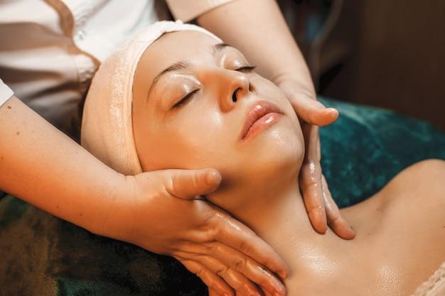 Mooie jonge vrouw die huidverzorgingsprocedures in een kuuroordsalon doet.