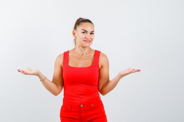 Mooie jonge vrouw die hulpeloos gebaar in rood mouwloos onderhemd toont en verward kijkt. vooraanzicht.