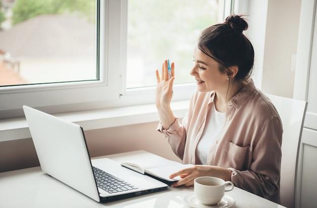 Mooie jonge vrouw die iemand op laptop begroet terwijl ze een boek leest en een kopje koffie drinkt aan het bureau in vrijetijdskleding