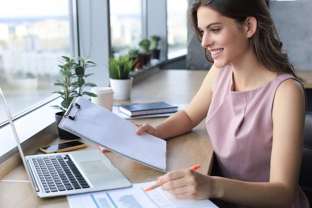 Mooie jonge vrouw die iets opschrijft terwijl ze in een modern kantoor zit.