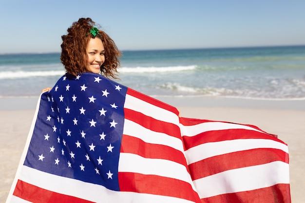 Mooie jonge vrouw die in amerikaanse vlag wordt verpakt die camera op strand in de zonneschijn bekijkt