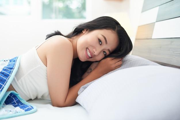 Mooie jonge vrouw die in bed ligt