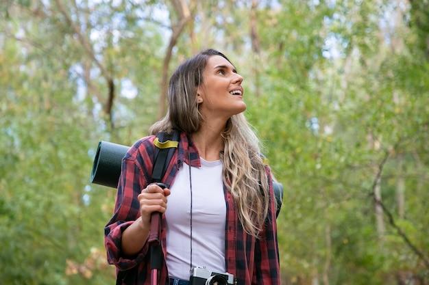 Mooie jonge vrouw die in bergen met rugzak wandelt. opgewonden vrouwelijke reiziger rondkijken en glimlachen. groen op de achtergrond. backpacken toerisme, avontuur en zomervakantie concept