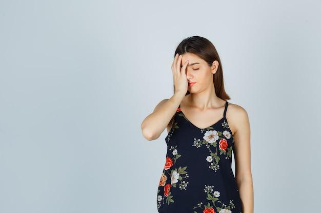 Mooie jonge vrouw die in blouse hand op gezicht houdt en moe kijkt
