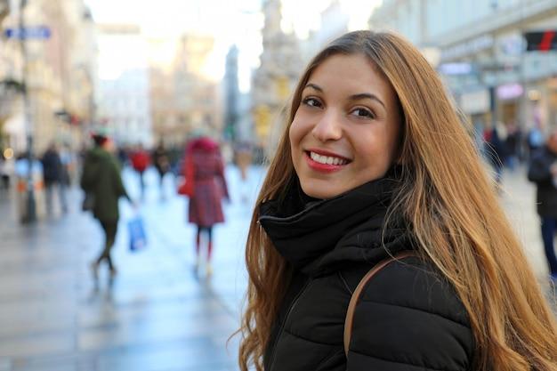 Mooie jonge vrouw die in de hoofdstraat van wenen bij winterseizoen, oostenrijk loopt