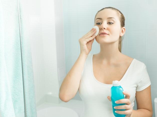 Mooie jonge vrouw die in de spiegel kijkt en reinigingslotion gebruikt