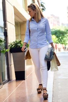 Mooie jonge vrouw die in de straat loopt. winkelconcept.