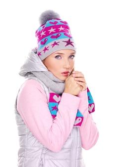 Mooie jonge vrouw die in de winterkleren haar handen verwarmt