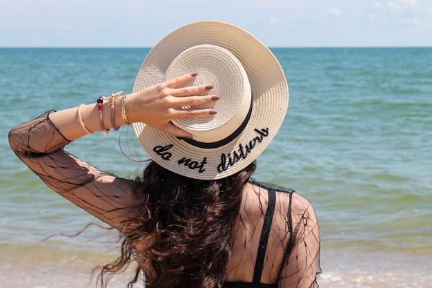 Mooie jonge vrouw die in de zomervakantie strohoed draagt die van het uitzicht op de oceaan geniet