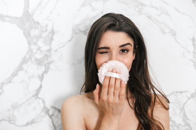 Mooie jonge vrouw die in een handdoek wordt verpakt die zich over marmeren muur bevindt, die poederdons gebruikt