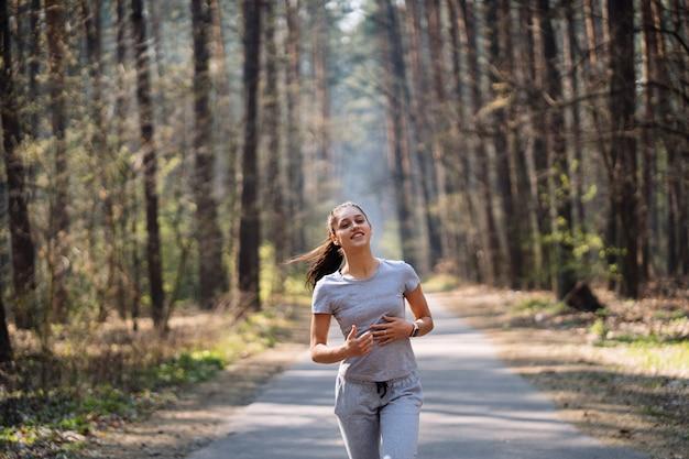 Mooie jonge vrouw die in groen park op zonnige de zomerdag loopt