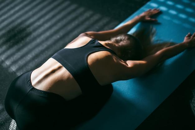 Mooie jonge vrouw die in gymnastiek uitwerken, die de voorwaartse oefening van de buigyoga op blauwe mat, close-up doen