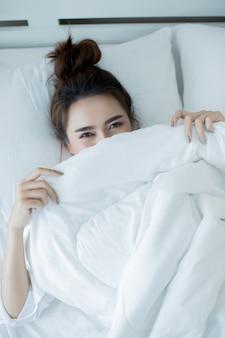 Mooie jonge vrouw die in het bed en het slapen ligt.