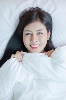 Mooie jonge vrouw die in het bed ligt.