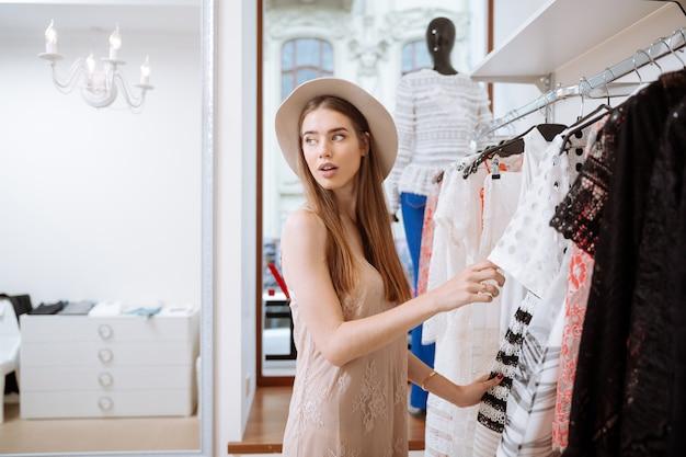 Mooie jonge vrouw die in hoed kleren kiest en het winkelen in klerenwinkel doet