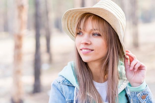 Mooie jonge vrouw die in hoed weg in openlucht kijkt