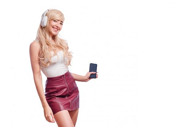 Mooie jonge vrouw die in hoofdtelefoons aan muziek het glimlachen luistert