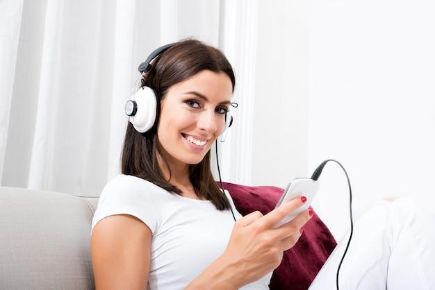 Mooie jonge vrouw die in hoofdtelefoons aan muziek luistert