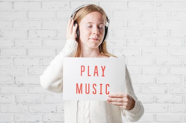 Mooie jonge vrouw die in hoofdtelefoons aan muziek op lichte muur luistert
