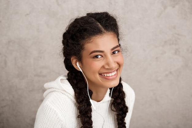 Mooie jonge vrouw die in hoofdtelefoons over beige muur glimlacht