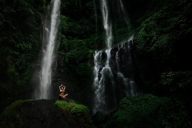 Mooie jonge vrouw die in lotusbloempositie mediteren terwijl het doen van yoga in een prachtig bos dichtbij waterval. mooie vrouwelijke beoefenen van yoga op rots in de buurt van tropische waterval