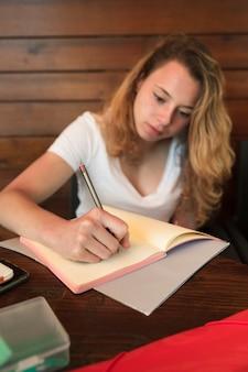 Mooie jonge vrouw die in notitieboekje schrijft