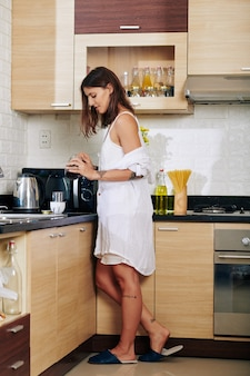 Mooie jonge vrouw die in ochtendtoga koffie in keuken maakt
