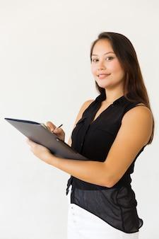 Mooie jonge vrouw die in omslag schrijft