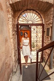 Mooie jonge vrouw die in oude gesmede poorten en smalle straat loopt