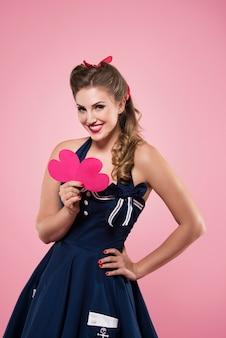 Mooie jonge vrouw die in pin-up stijlkleren hartvormen houdt