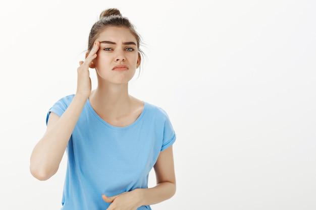 Mooie jonge vrouw die in spiegel kijkt, teleurgesteld voelt in haar gezichtsuitdrukkingen