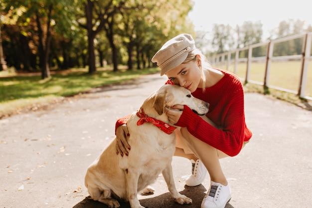 Mooie jonge vrouw die in stijlvolle kleding haar hond teder kust. mooie blonde met haar huisdier genieten van zonnig weer in het park.