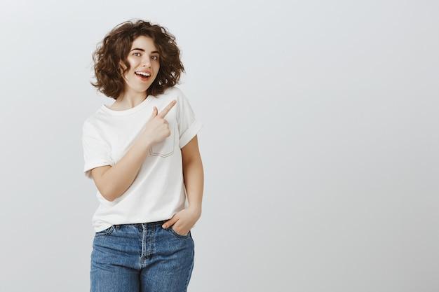 Mooie jonge vrouw die in vrijetijdskleding de rechterbovenhoek van de vinger richt, die controleproduct uitnodigt