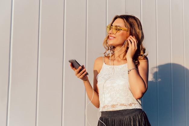 Mooie jonge vrouw die in zonnebril aan muziek in oortelefoons op haar telefoon luistert
