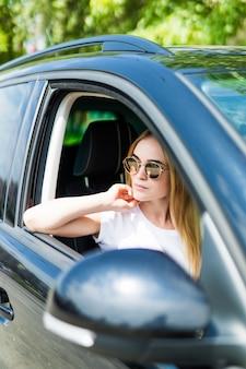 Mooie jonge vrouw die in zonnebril haar auto drijft