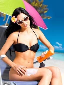 Mooie jonge vrouw die in zwarte bikini zonnebrandcrème toepast op het gebruinde lichaam.