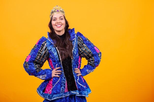 Mooie jonge vrouw die inovatinekostuum over gele achtergrond in studio draagt