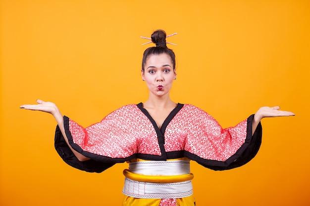 Mooie jonge vrouw die japans kostuum over gele achtergrond draagt