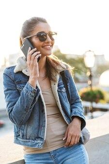 Mooie jonge vrouw die jas draagt die buiten in de stadsstraat loopt, mobiele telefoon overneemt