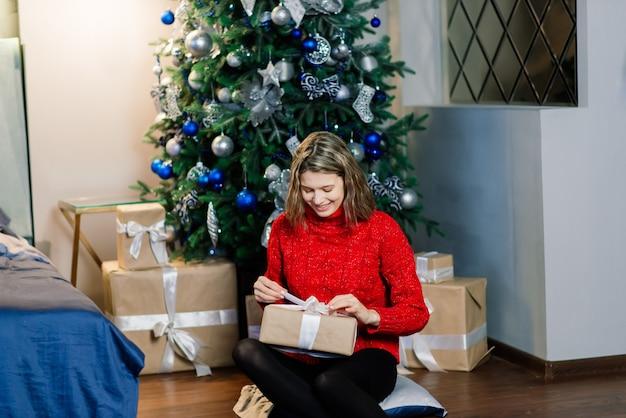 Mooie jonge vrouw die kerst thuis viert, plezier heeft tijdens het openen van cadeautjes
